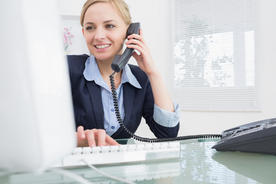 Young female executive using phone and computer at desk in office