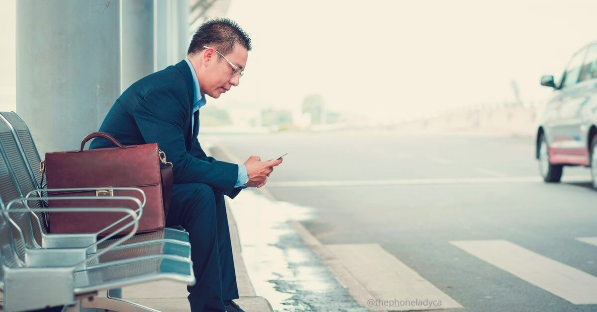 man waiting for taxi catching up on email