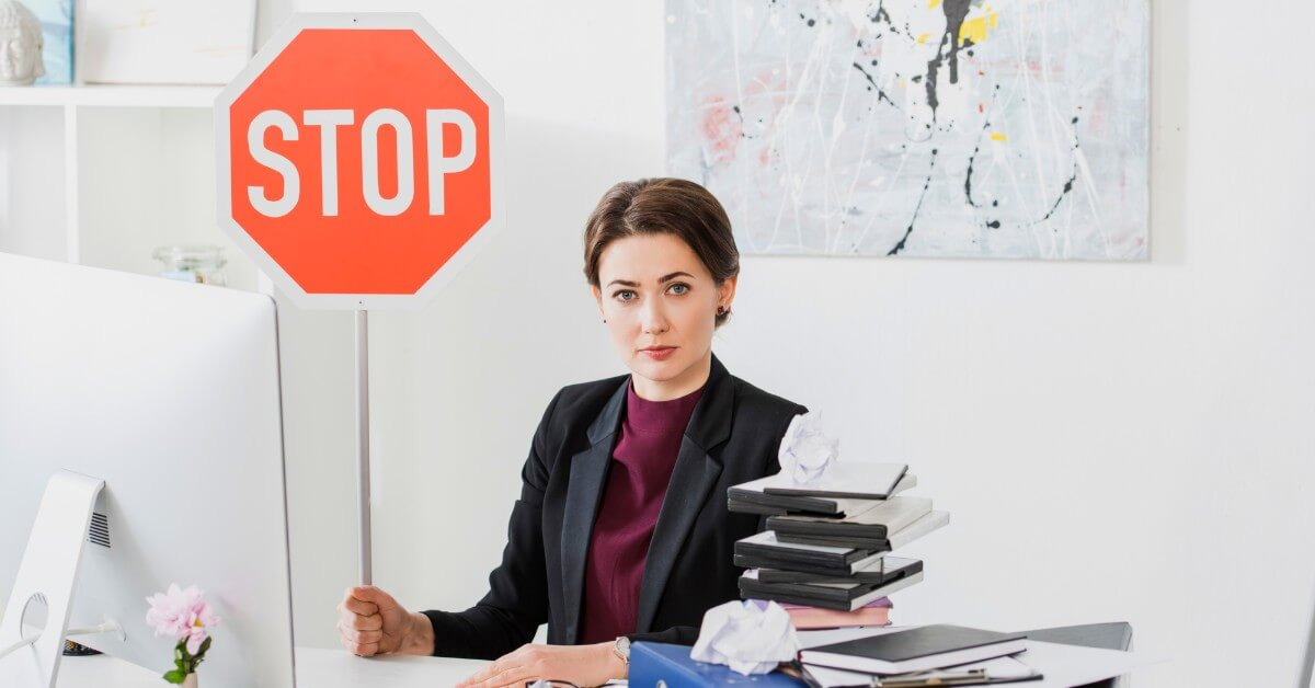 woman at desk holding stop sign